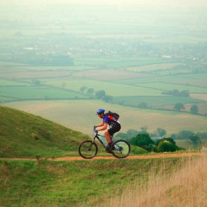 An image of an adult cycling on top of a hill, with a beautiful coutryside view behind them.